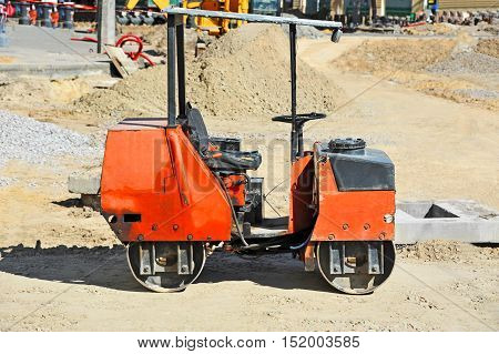 Red asphalt paver on road construction site