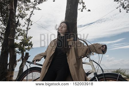 Portrait of beautiful brunette girl wearing raincoat on beach with bicycle