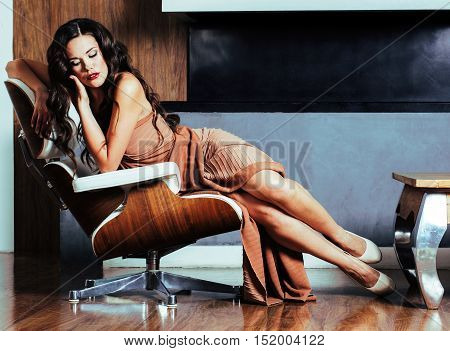 beauty young brunette woman sitting near fireplace at home, winter warm evening in interior, waiting to celebrate, lifestyle poeple concept close up