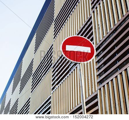 stop sign near new parking building, empty street nobody concept close up