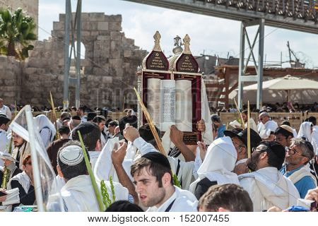 JERUSALEM, ISRAEL - OCTOBER 12, 2014: The area in front of Western Wall of Temple filled with people. Jews for ritual tallit worship with prayer books. Imposition of a Torah scroll for prayer