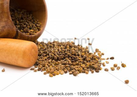 wooden mortar and pestle with flos chrysanthemi indic on white background close up