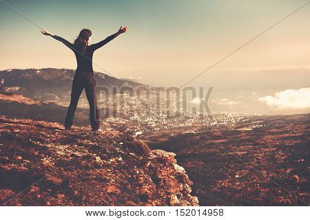 Woman standing on top of a mountain, back view