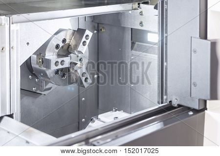 The CNC lath machineclose up to the head stock of CNC lath machine.The CNC turning machine without the work pieces in low light scene