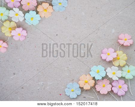 Colorful pastel artificial flower on recycled paper background floral card decoration