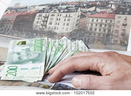 Hand holding swedish currency symbolising the expensive flats in the housing ad