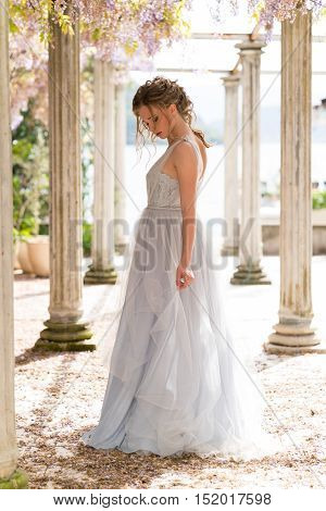 young bride in a wedding dress poses on the terrace with columns