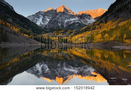 Beautiful sunrise touches Maroon bells peak at Maroon lake Aspen Colorado. Fall color of Aspen and reflection of Maroon Bells