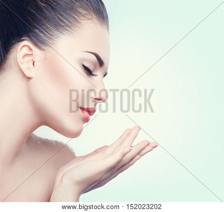 Beauty Spa Woman with perfect skin Portrait. Beautiful Brunette Spa Girl showing empty copy space on the open hands palm for text. Proposing a product. Gestures for advertisement. Blue background