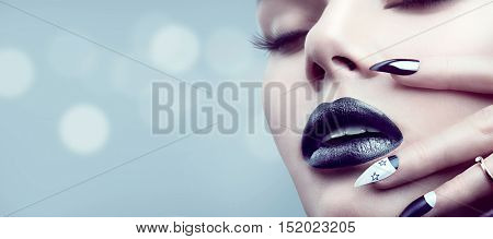 High Fashion Model Girl Portrait with Trendy gothic Black Make up, dark Manicure and accessories. Halloween Vampire Woman portrait with black matte lips and nails over deep blue background