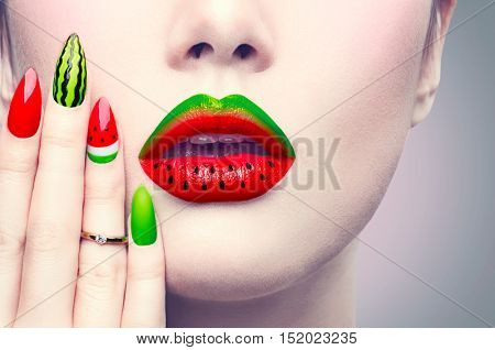 Trendy Watermelon summer or autumn Manicure and Lips. Beauty Fashion Makeup and Manicure. Glamour Nail Art and Make up closeup over gray background