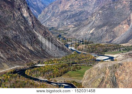 The picturesque autumnal top view on the mountains cliffs and beautiful winding river in a valley between the mountains