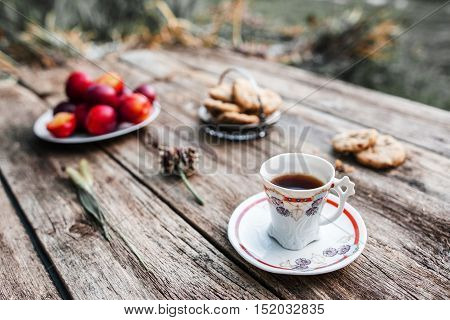 Cup of coffee on wooden table outdoor, Focus on cup, blurred background of fresh plums, cookies and green nature environment