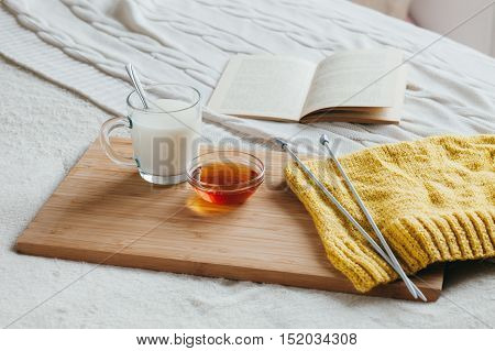 Hot milk in a glass cup and honey on a wooden board. Treatment of hot drink. Treatment of folk remedies in bed. Knitting needles and yarn for knitting. The book to read.