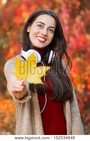 Girl holding autumn orange maple leaf. Beautiful young brunette woman with maple lleaf in her hands spending time in the autumn park. Smiling girl holding yellow maple leaf on the background colorful autumn forest. Autumn.