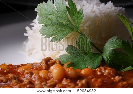 Chili con carne with rice and leaf parsley on white plate.