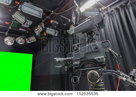 Television studio with camera and lights - camera on green screen