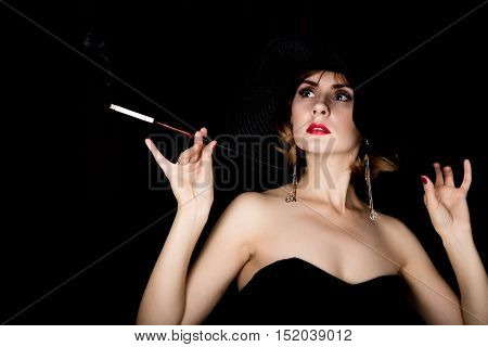 Beauty retro female model with professional makeup and mouthpiece in hand. fashion vintage woman on a dark background.