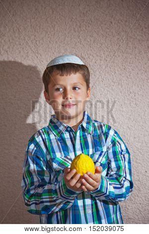 Sukkot. Adorable Jewish boy wearing a white skull cap holds a ritual fruit - Etrog