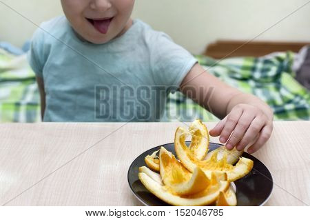 Cropped portrait of a little girl picking up an orange with a tongue sticking out unmade bed in the blurred background