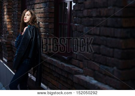 Lifestyle fashion portrait of brunette girl in rock black style, standing outdoors in the city street.