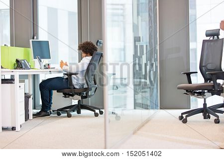 Full length side view of young businessman sitting on chair at desk in office