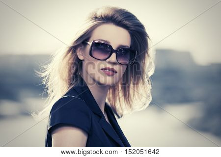 Portrait of young woman in sunglasses. Stylish fashion model walking outdoor
