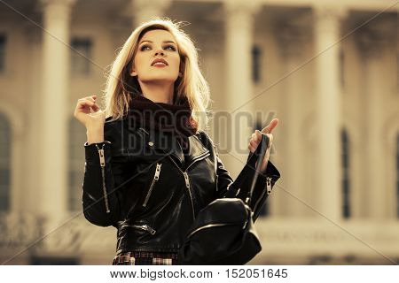 Young blond woman in leather jacket walking on city street. Stylish fashion model with handbag outdoor
