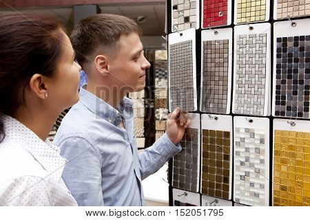 Couple pointing at ceramic mosaic tile for bathroom wall in store, in home improvement warehouse exterior