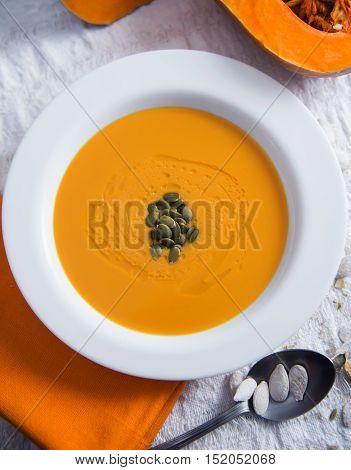 Autumn pumpkin soup on a light background