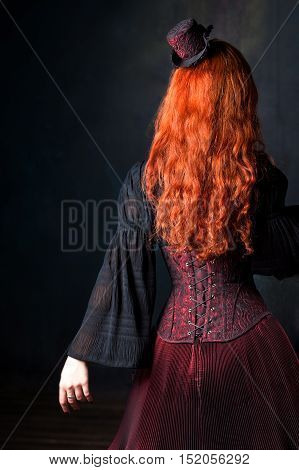 Slender red-haired girl in corset and hat
