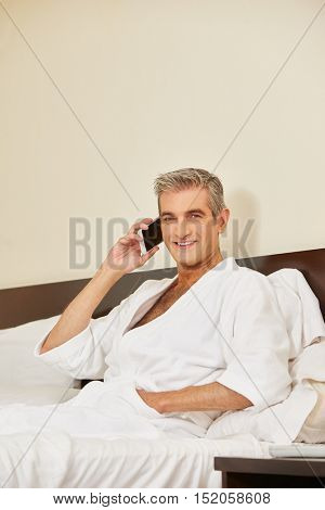 Elderly man using his smartphone to make a phone call in a hotel room
