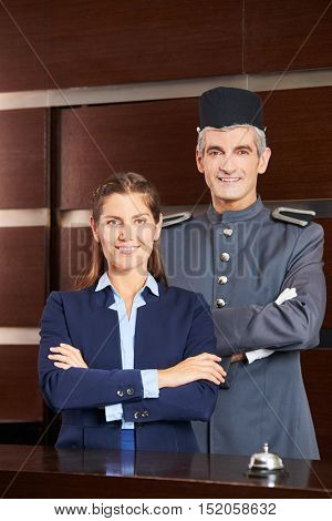 Concierge and receptionist in hotel smiling at reception