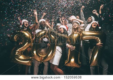 Celebrating New Year. Group of cheerful young people in Santa hats carrying gold colored numbers and throwing confetti
