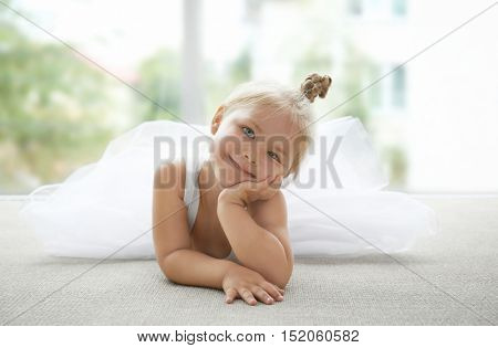 Cute little girl lying in ballet class