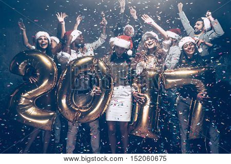 New Year is coming! Group of cheerful young people in Santa hats carrying gold colored numbers and throwing confetti