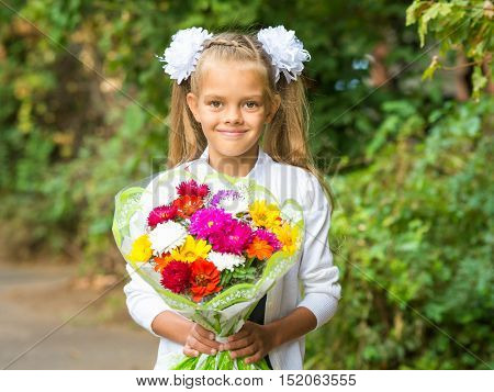 Up Portrait Of A Seven-year School Girl With A Bouquet Of Flowers