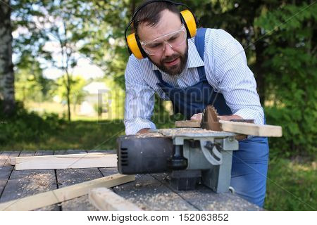 worker beard man with circular saw outdoor
