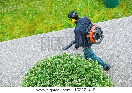 Houilles, France - April 08, 2014 : gardener using a gas blower in a park