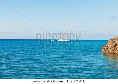 Sailboat and dingy at blue open sea