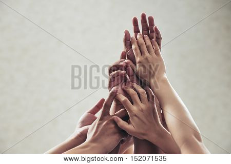 Many hands reaching up, isolated on beige