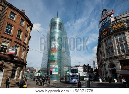 Manchester UK - September 23 2016: National Football museum at the Urbis building in Manchester city in England near the exchange square with people crossing the street.
