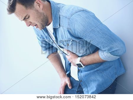 I hate pain. Young good looking man opening his mouth and having stomachache while standing near the wall.