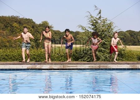 Group Of Children Jumping Into Outdoor Swimming Pool