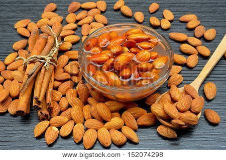 Raw almonds soaking in a white bowl of water