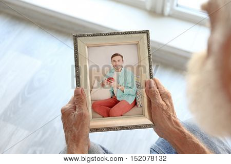Elderly man holding photo frame with picture of grandson. Happy memories concept.