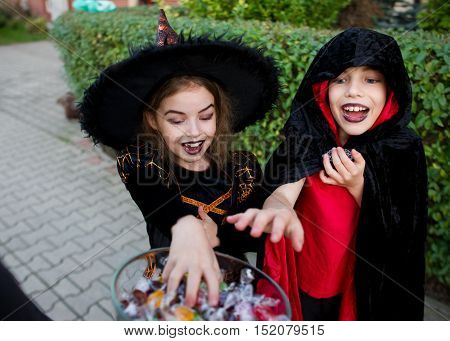 Girl in a suit of the sorcerer and the boy in a black-red cloak of the magician delay hands to vase candies. On the children's faces frightening make-up. Children delighted with the event.