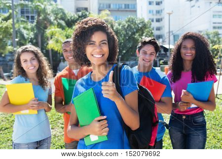 Group of five modern latin american caucasian and african students outdoor in the city in summer