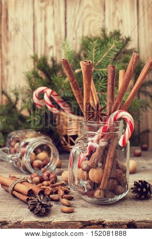 Winter spices and ingredients for cooking the Christmas meal. Cinnamon sticks hazelnuts walnuts anise stars Christmas tree branches on old wooden background
