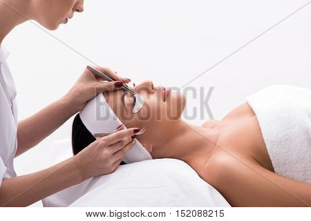 I trust only to professionals. Cropped shot of attractive woman lying on couch in beauty salon during eyelash extension procedure, isolated on white background